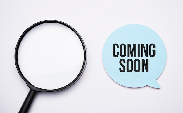 Coming soon speech bubble and black magnifier isolated on the yellow background.