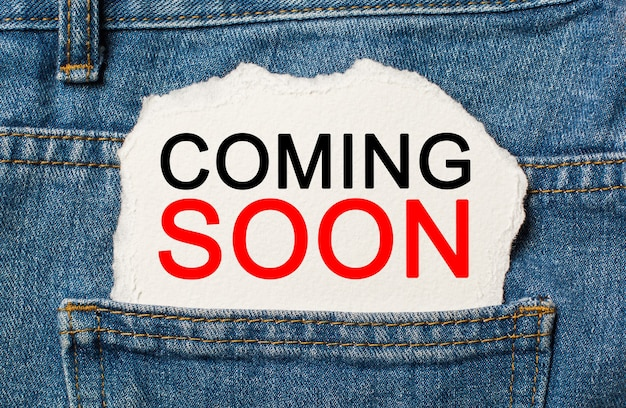Coming soon on torn paper wall on jeans business and finance concept