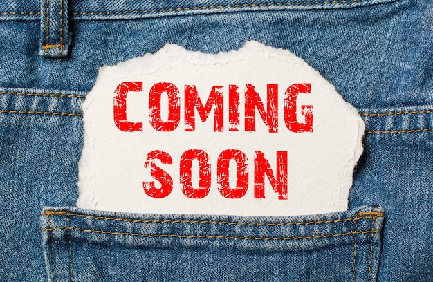 Coming soon on white paper in the pocket of blue denim jeans