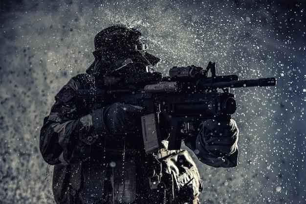 Боец-коммандос, профессиональный наемник, солдат спецназа с замаскированным лицом, заряженный боеприпасами, вооруженная штурмовая винтовка, патрулирует секретную миссию, крадется в темноте, готовый к бою