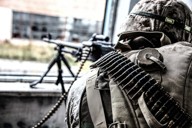 Commando machine gunner, u.s. marine corps infantryman, military squad automatic weapon operator in helmet and ammo belt around body, firing through window in ruined building, over shoulder back view