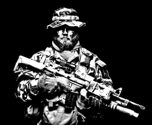 코만도 슈터, 전투복을 입은 육군 특수부대 소총수, 부니 모자, 로드 캐리어의 탄약, 페인트 얼굴로 위장, 무장 돌격 소총, 검은 배경에 절반 길이 초상화
