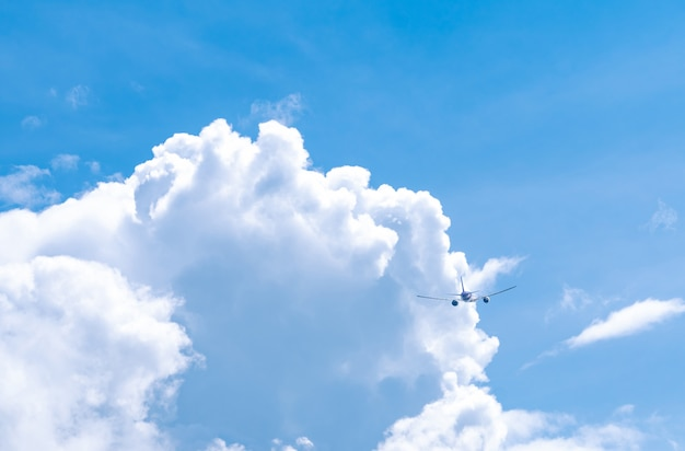 Commercial airline flying on blue sky and white fluffy clouds
