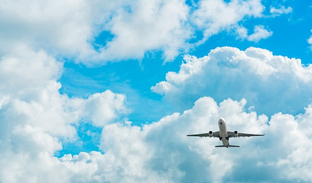 Commercial airline flying on blue sky with white fluffy clouds.