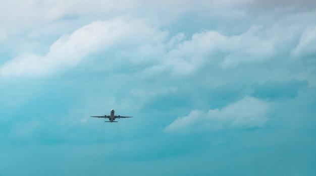 Коммерческая авиакомпания. пассажирский самолет взлетает в аэропорту с красивым голубым небом и белыми облаками. покидая рейс. начните путешествие за границу. отпуск. счастливой поездки.