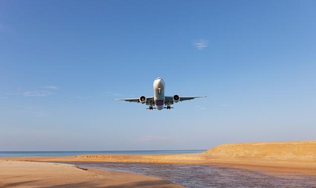 Коммерческий самолет приземляется над морем в летний сезон и ясное голубое небо над красивыми пейзажами