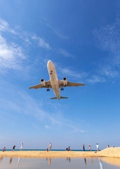 Commercial airplane landing above sea and clear blue sky