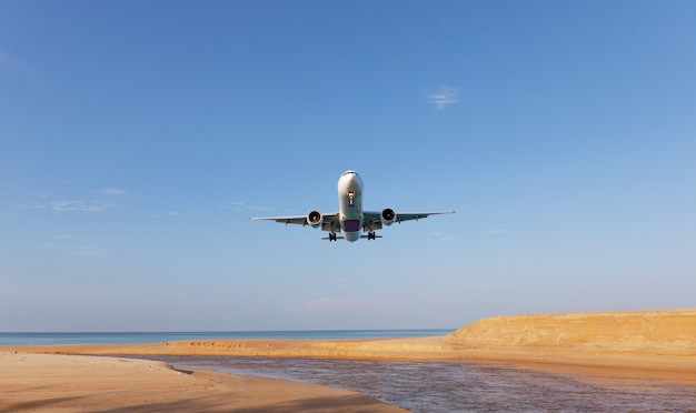 Commercial airplane landing above sea in summer season and clear blue sky over beautiful scenery