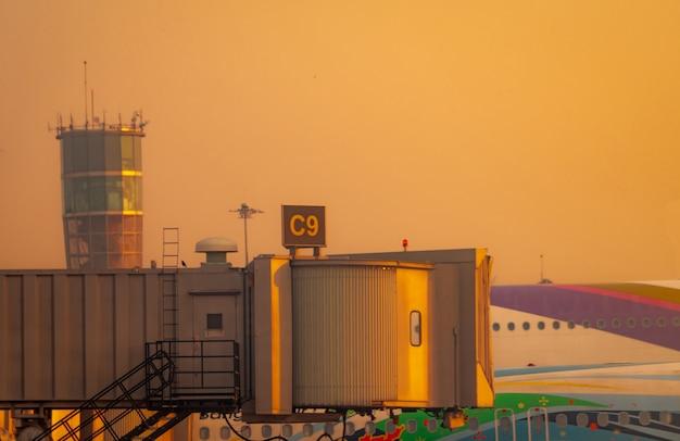 旅客機が空港で離陸するためにジェットブリッジに駐機している民間航空機。空港の航空管制塔の近くの黄金の夕焼け空とドッキングした航空機の旅客搭乗橋。