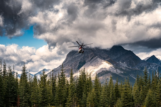 Commercial helicopter flying with dark sky into the assiniboine provincial park