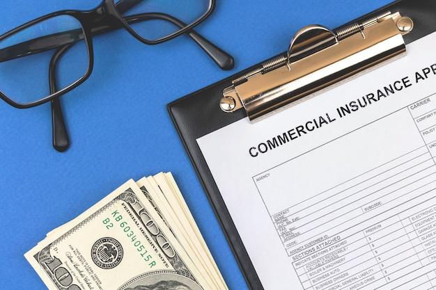 상업 보험 청구 양식입니다. 공식 계약 및 재산 계약이 있는 사무실 책상. 돈과 클립보드가 있는 데스크탑. 상위 뷰 사진