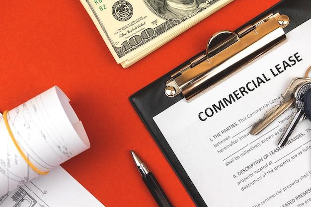 Форма коммерческой аренды. буфер обмена с деловым документом, ручкой и деньгами. красный фон, копия космического фото