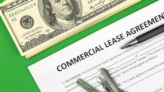 Крупный план формы коммерческой аренды. доллары, ручка и ключи от дома на зеленом офисном столе. фото вид сверху