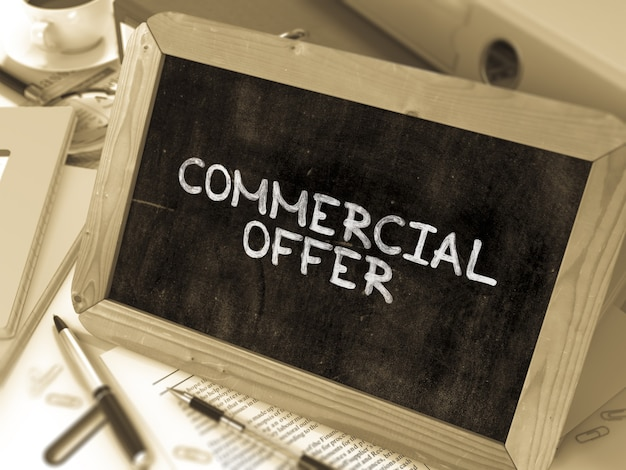 Commercial offer handwritten by white chalk on a blackboard. composition with small chalkboard on background of working table with office folders, stationery, reports. blurred, toned image. 3d render.