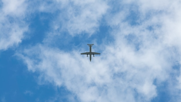 A commercial passenger aircraft across flying over head. jet airplane flying low with blue sky and clouds at background. plane fly in day time
