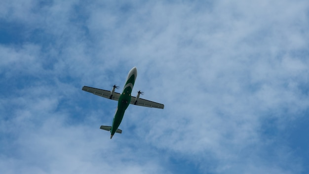 A commercial passenger propeller aircraft across flying over head. jet airplane flying low with blue sky and clouds at background. plane fly in day time