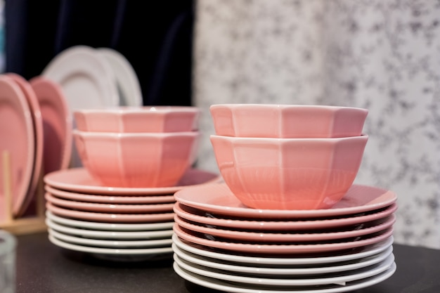 Commercial pink and white plates and bowls stacked with crystal wine glasses