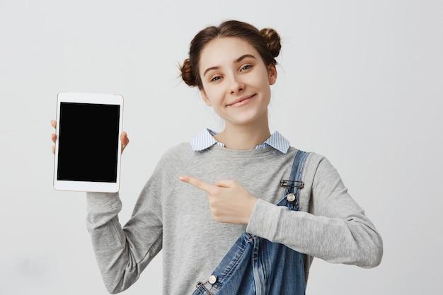 タブレットガジェットの画面に切り替えながら表示しながら笑顔の美しい女性とコマーシャル。おだんごパンのあるスマートな女の子は、その作業性を示す最新のデバイスを提示します。マーケティング販売