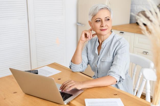 コミュニケーション、テクノロジー、仕事、年齢、退職の概念。キッチンカウンターに座って、ラップトップでキーボード操作し、インターネット経由で生計を立てている集中した深刻な自営業の女性年金受給者