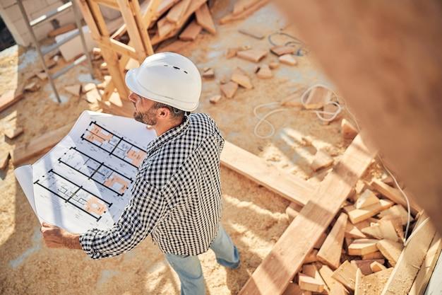 家の設計図をチェックする献身的なビルダー
