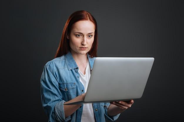 献身的な従業員。自宅で仕事をし、レポートを熟読しながらラップトップを採用しているスマートカリスマ的な明るい女性