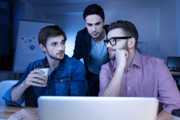 Committing cybercrime. smart handsome male hackers working together and looking at each other while hacking into a website