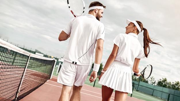 Молодая пара с общими интересами собирается поиграть в теннис на корте