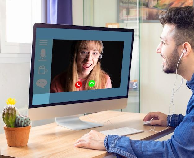 ビデオチャットでコンピューター上の彼のガールフレンドと通信します。ウェブカメラを通して女の子と話します。