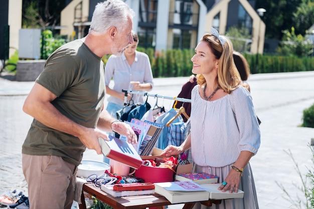 Общение с женщиной. бородатый седой мужчина общается с красивой женщиной на распродаже во дворе, покупая старые книги