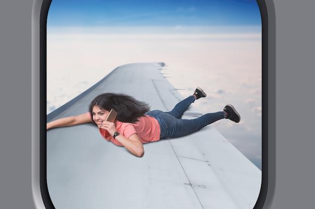 Зависимость от общения, молодая женщина с телефоном лежит на крыле самолета в полете, небо и облака на фоне