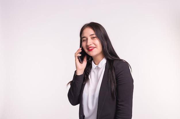 커뮤니케이션 및 사람들 개념. 젊은 갈색 머리 여자 모바일에 얘기 하 고 복사 공간 흰색에 웃 고