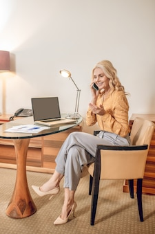 コミュニケーション。手に電話を持って肘掛け椅子に座っている金髪のきれいな女性