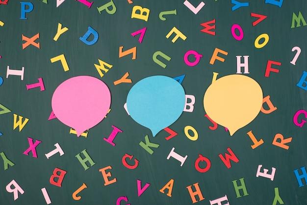 Концепция коммуникации. фотография трех красочных пузырей мысли, изолированных на зеленой доске с разноцветными буквами