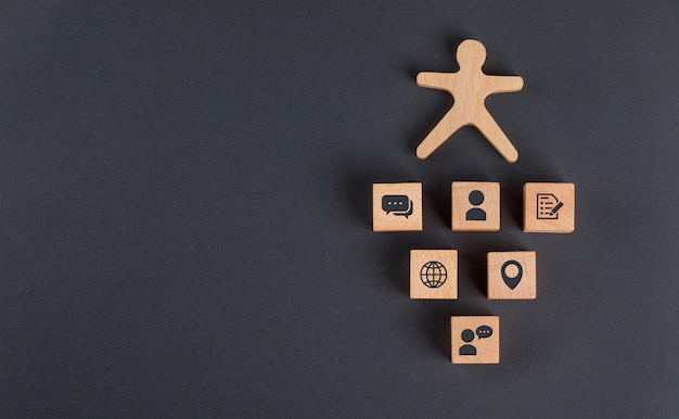 Communication concept with icons on wooden cubes, human figure on dark grey table flat lay.