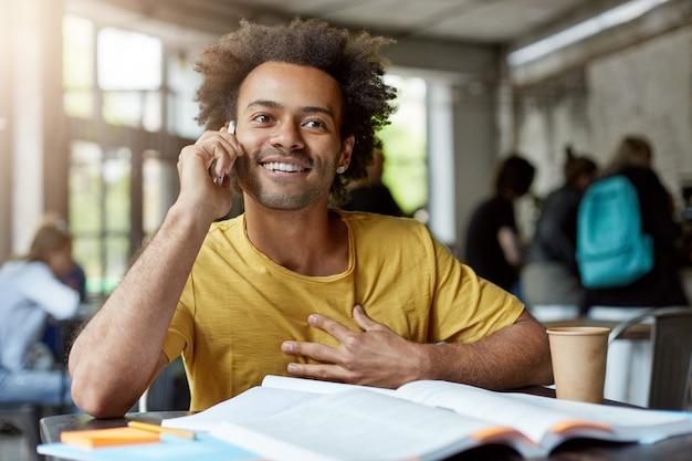 コミュニケーション、教育、現代技術。魅力的な肯定的な浅黒い肌の学生で、アフロのヘアカットが教科書のあるカフェのテーブルに座って電話での会話を楽しんでいる