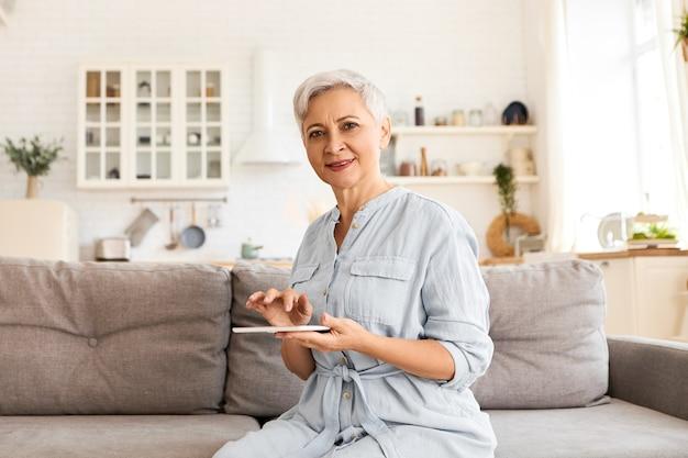 通信、電子機器、ネットワーキング。デジタルタブレットを使用してインターネットをサーフィンしたり、オンラインで買い物をしたり、電子書籍を読んだりして、長い青いドレスを着たモダンでスタイリッシュな引退した60歳の女性