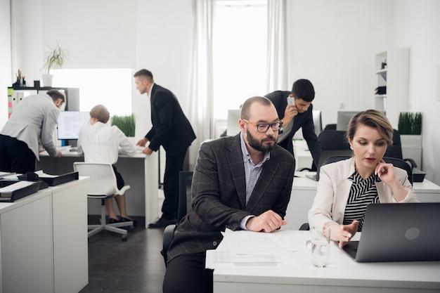 テーブルのオフィスで金融会社のクライアントと取引を行うためのコミュニケーション。セールスマネージャーとバイヤー。