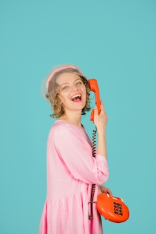 Communication girl talking on landline phone smiling girl talking on retro phone happy woman in pink