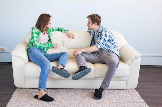 통신, 레저 및 관계 개념-웃으면 서 소파에 얘기하는 재미 젊은 부부.