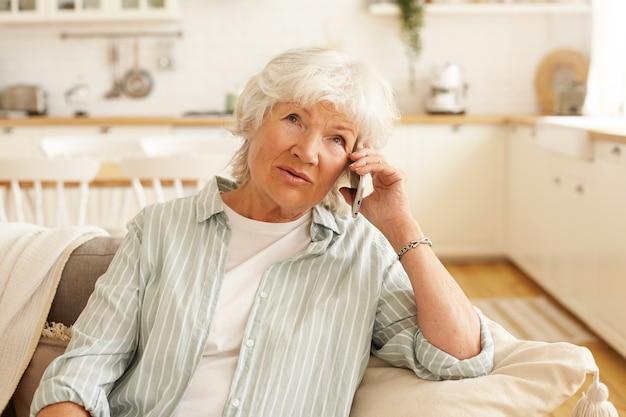 コミュニケーション、最新の電子機器、老朽化の概念。携帯電話を持って、娘と話し、広く笑って、良いニュースを受け取っている美しいカジュアルな服装の白人女性年金受給者