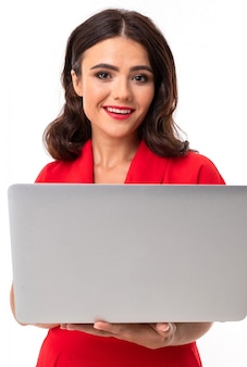 Communication network. brunette in a red dress on an isolated  holds a laptop in hands