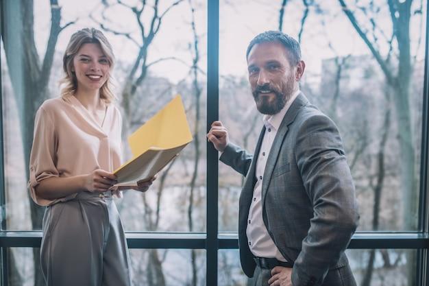 コミュニケーション、パートナー。フォルダーとビジネスの同僚の笑顔の男が窓の近くに立って通信しているうれしそうなかなり若いブロンドの女性