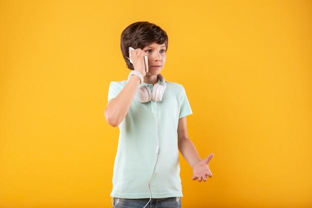 コミュニケーション。電話で話している間微笑んでいる深刻な黒髪の少年