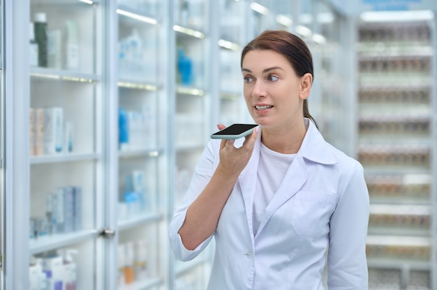 Communication. serious long-haired adult woman in white coat looking at shelves with medications talking into smartphone standing in pharmacy
