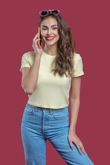 コミュニケーション、スマートフォン。陽気な気分でスマートフォンで話しているカジュアルな服を着た長い巻き毛の美しい手入れの行き届いた若い女性