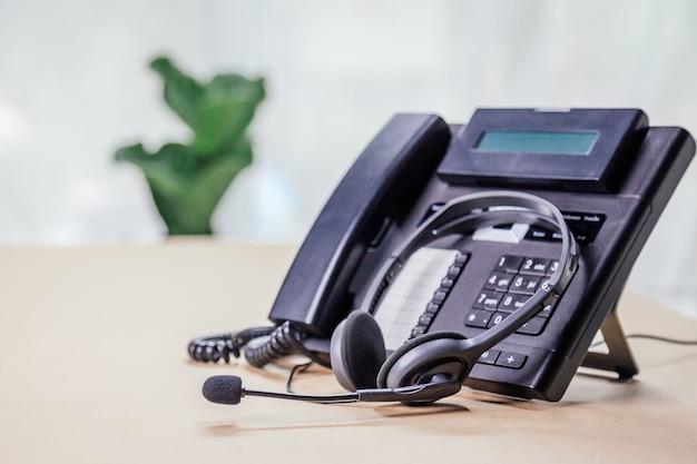 コミュニケーションサポート、コールセンター、カスタマーサービスヘルプデスク。オフィスにvoipヘッドセットを備えた電話デバイス。カスタマーサービスサポート(コールセンター)の概念。