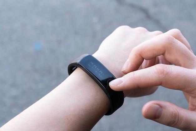 Концепция коммуникационных технологий крупным планом женщина настраивает умные часы перед тренировкой.