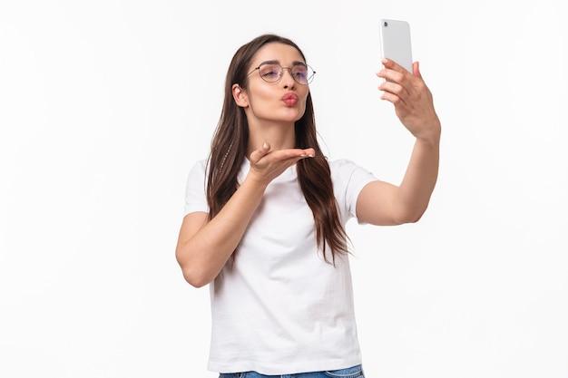 コミュニケーション、テクノロジー、ライフスタイルのコンセプト。眼鏡をかけた素敵な魅力的な女性、空気を送る
