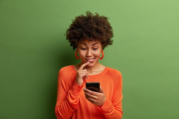 커뮤니케이션, 기술, 라이프 스타일 개념. 호기심이 많은 어두운 피부의 여성이 온라인에서 흥미로운 게시물을 읽고, 휴대 전화를 손에 들고, 수신 된 메시지에 대한 답변을 제공하는 방법을 생각하고, 실내 포즈를 취합니다.