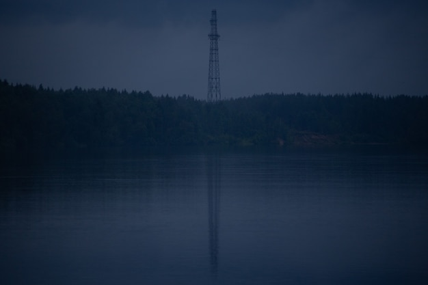 강둑의 통신 타워와 물에 반사